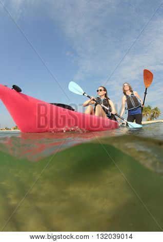 Young women in kayak in ocean in florida