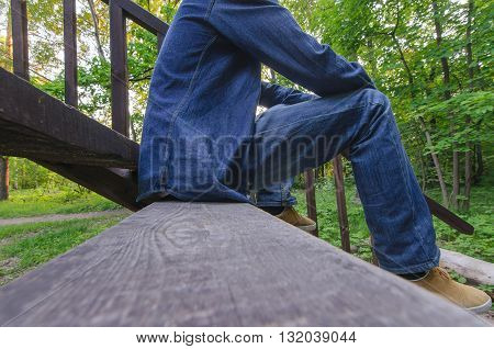 Beautiful young men in jeans sitting on stairway