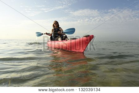 young woman in pink kayak with blue paddle in ocean