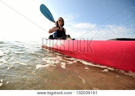 Pretty young woman having fun in a pink kayak