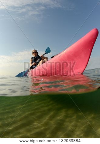 Young woman in pink kayak in Atlantic Ocean