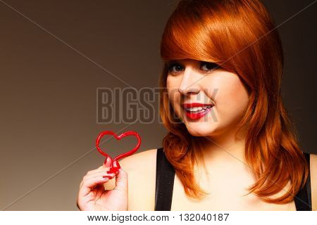 Love to candy and sweets. Valentine's Day concept. Gorgeous young woman holding candy heart on brown background in studio.