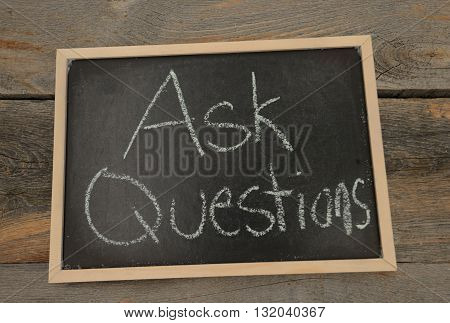 Ask Questions written in chalk on a chalkboard on a rustic background