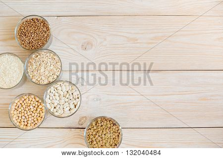 Grain and beans in glass bowls on a white wooden background. Various types of grain. beans, peas, buckwheat, lentils, rice. background of white boards. healthy food and diet concept. top view
