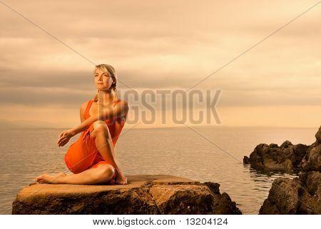 Bella joven haciendo ejercicio de yoga al aire libre