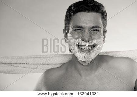 Portrait of happy man with half shaved face beard hair. Smiling handsome guy on blue. Skin care and hygiene. Black and white photo.