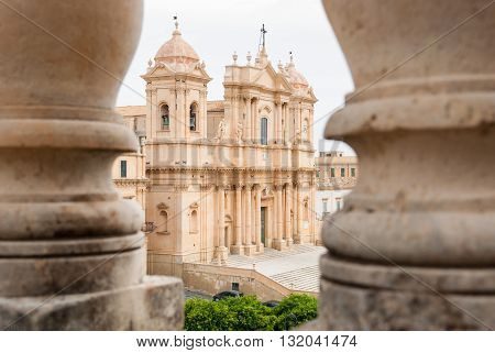The baroque cathedral of Noto (UNESCO site in Sicily) seen through two columns