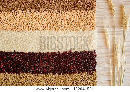 Grain and beans stripes on a white wooden background. Various types of grain. beans, peas, buckwheat, lentils, rice. healthy food and diet concept. Grain abd beans background. top view