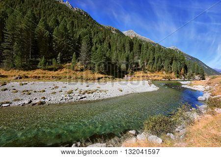Headwaters of the famous Krimml waterfalls. Bluish - green transparent water glows in the midday sun. Austrian Alps
