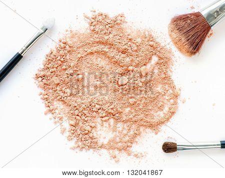 Island of crushed powder with make-up brushes set on white