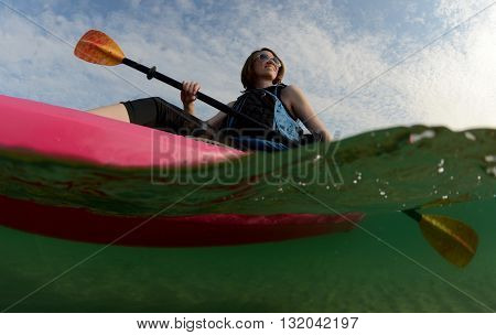 Young woman on pink kayak in ocean
