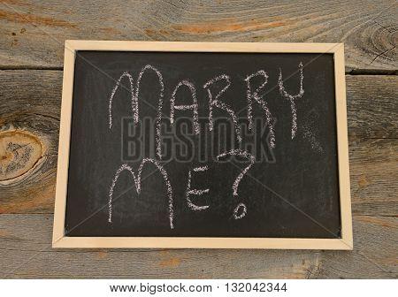 Marry me written in chalk on a chalkboard on a rustic background