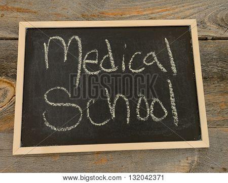 Medical school written in chalk on a chalkboard on a rustic background