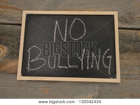 Anti-bully message or no bullying written in chalk on a chalkboard on a rustic background