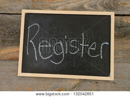 Register written in chalk on a chalkboard on a rustic background