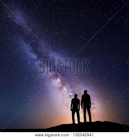 Milky Way with silhouette of a family with yellow light on the mountain. Father and a son. Night landscape. Beautiful Universe. Space. Travel background with sky full of stars