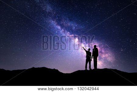 Milky Way with silhouette of a family on the mountain. Father and a son who pointing finger in night starry sky. Night landscape. Beautiful Universe. Space. Travel background with sky full of stars