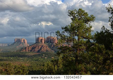 Stormy clouds over Sedona Arizona with green trees in foreground