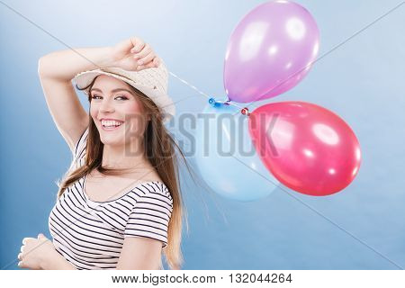 Woman joyful girl playing with colorful balloons. Summer celebration and lifestyle concept. Studio shot blue background