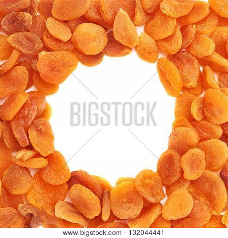 Round shape made of dried orange apricots over isolated white background, top view