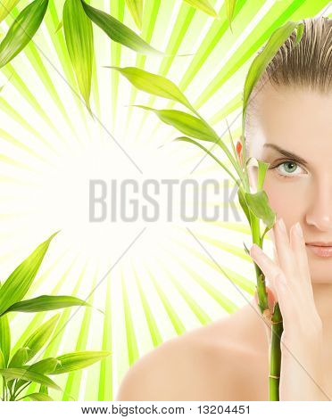 Beautiful young woman with bamboo plant over abstract green background
