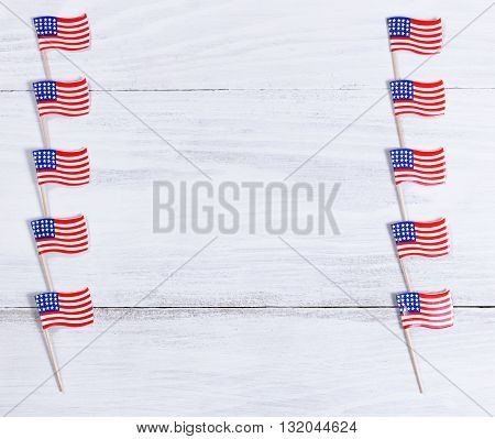 Small USA flags lined up on right and left sides of rustic white wooden boards. Fourth of July holiday concept for United States of America.