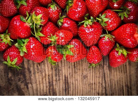 food background with plenty of ripe strawberry on old wooden table, close up
