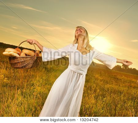 Bela jovem com um cesto cheio de pão fresco