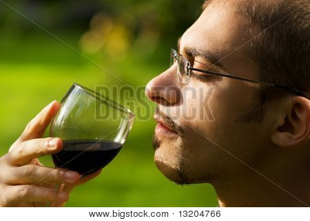 Professional sommelier tasting red wine. Close-up portrait.