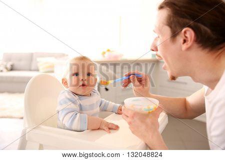 Father feeding his baby son