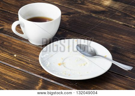 Empty white plate with crumbs and fat stains after vanilla cream cake was eaten