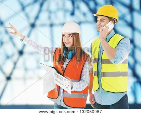 Two architects at work on blurred construction background
