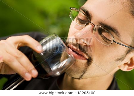 Handsome young man drinking red wine