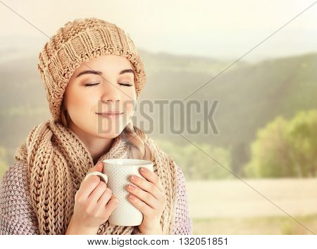 Beautiful girl enjoying a cup of tea on blurred mountains background