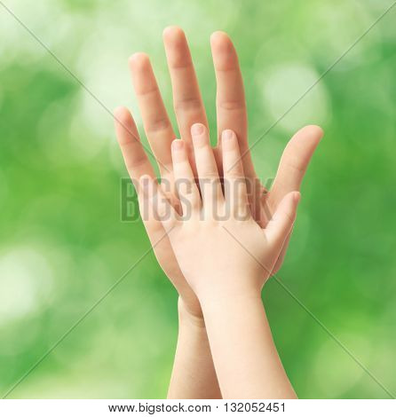 Child and dad  hands on green nature background. Concept of taking care, protection, helping and assistance