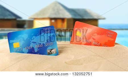 Red and blue bank cards in sand on blurred resort background