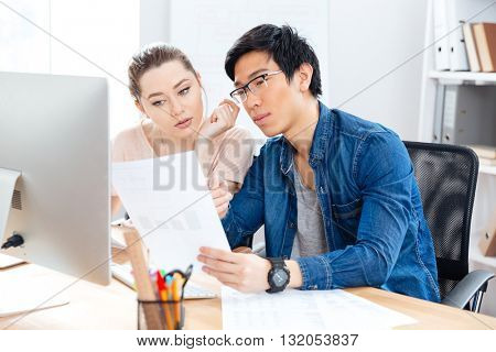 Two serious young businesspeople working with documents in office together