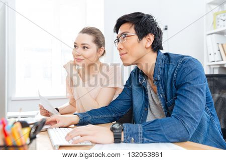Happy young woman and asian man in glaases working with computer together