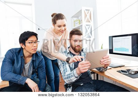Three focused young businesspeople working in office together and using tablet