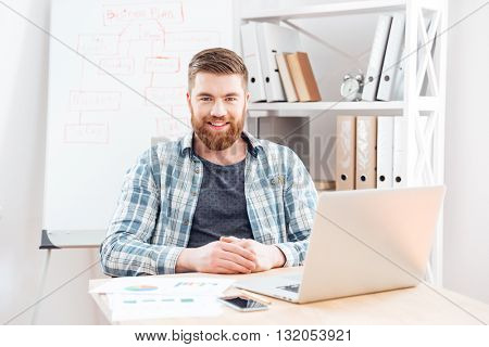 Cheerful bearded young businessman making business plan and working with laptop in office