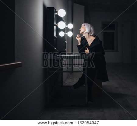 Full length of beautiful blonde young woman in black coat looking at the mirror and applying lipstick in dressing room