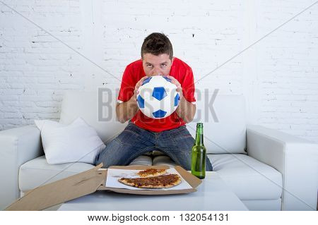 young man alone holding ball and kissing it in stress wearing team jersey watching football game on television at home living room sofa couch excited and anxious eating pizza drinking beer