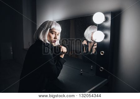 Beautiful young woman in blonde wig and black coat sitting in dressing room