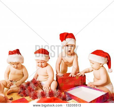 Group of adorable toddlers in Christmas hats packing presents. Isolated on white background