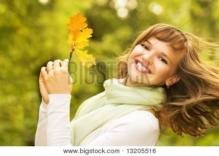 Beautiful romantic brunette with golden autumn leaf close-up portrait
