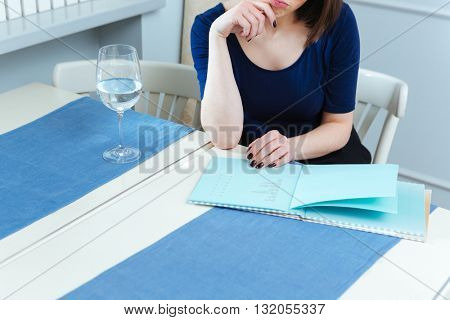 Thoughtful young woman looking through menu and thinking in cafe