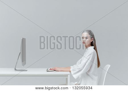 Mystic cosmic woman sitting at the desk with computer, pc over gray background