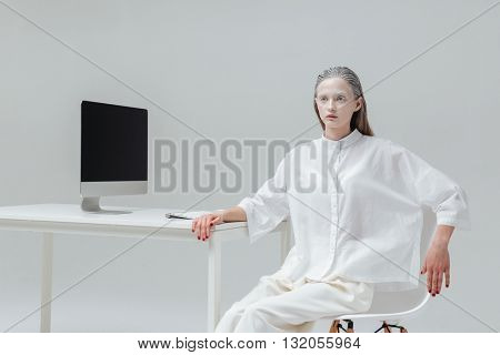 Beautiful fashion pretty woman relaxing at the table with computer on the chair over gray background