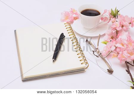 Open diary a pencil is placed on top and glasses placed side by side pink flower with cup of coffee.