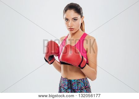 Sports woman in boxing gloves looking at camera isolated on a white background